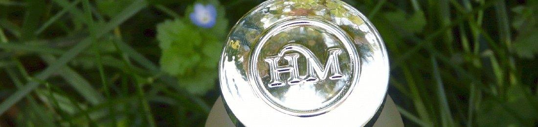 Letras HM brillando sobre un fondo de hierbas