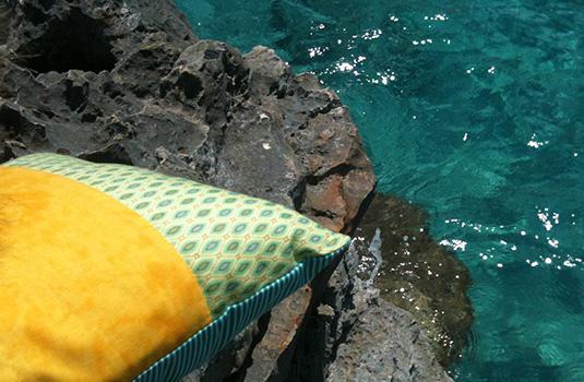 Almohada perfumada Hierbas de Mallorca al sol en unas rocas junto al mar