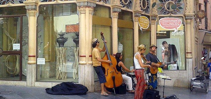 Músicos tocando en la calle frente a edificio historico de Palma