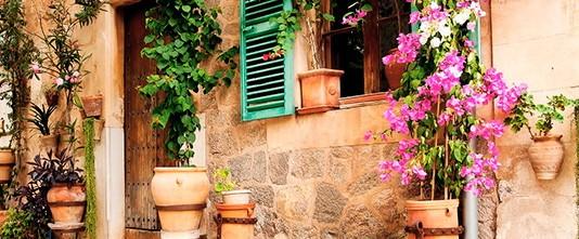 Ventana adornada con flores en maceta, un rincón con encanto de una callejuela mallorquina