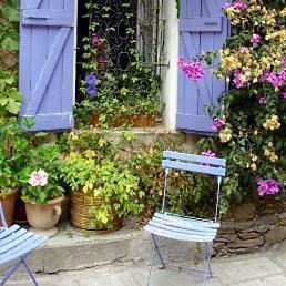 Sillas azules bajo la ventana para un encuentro apacible reodeados de flores