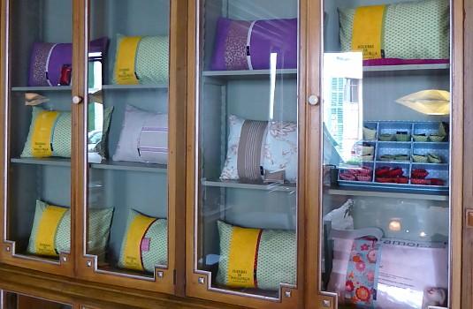 Vitrina antigua exponiendo diferentes diseños de almohadas hechas a mano